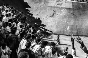 Axum. Dopo la veglia durata tutta la notte, i sacerdoti hanno benedetto un grande bacino d'acqua. Centinaia di persone si accalcano sulle sue rive e corrono giù dalle ripidissime sponde del laghetto per fare il bagno e raccogliere nelle bottiglie l'acqua benedetta.