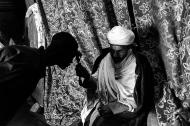 Lalibela. Il sacerdote vestito con i paramenti liturgici, avvolto dai tendaggi che nascondono il Tabot, benedice un fedele durante i festeggiamenti di San Giorgio.