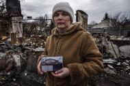 © Giorgio Bianchi - Vera Andreyvna mostra una foto della sua abitazione scattata prima che questa fosse colpita da una bomba al fosforo. Ogni giorno Vera fa visita ai suoi cani che ancora vivono nel cortile della casa per nutrirli ed accudirli.